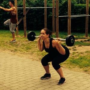 Kvinde, der løfter en vægtstang under træning hos Coach Mølvad